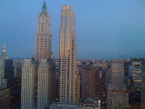 A View Of Several Buildings Including The Woolworth Building At Dusk