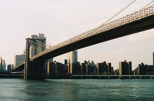 The Brooklyn Bridge Spans Out Over The Water On And Overcast Day