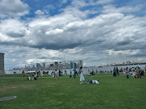 People Hang Out On The Lush Green Fields Of Liberty Island On A Cloudy Evening.