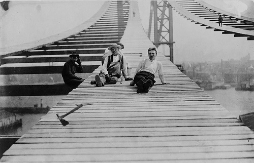 Four Men Working On Footpath On New Manhattan Bridge Above The East River In New York City.
