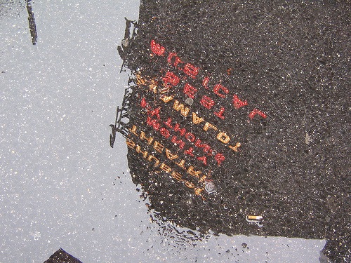 A Reflection Of The Broadway Theatre In A Rain Puddle.
