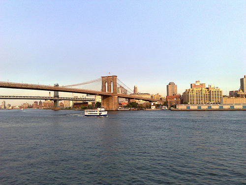 A Tourist Boat Passes Under The Famed Brooklyn Bridge.