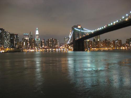 Water Looks Like Glass Underneath The Brooklyn Bridge At Night