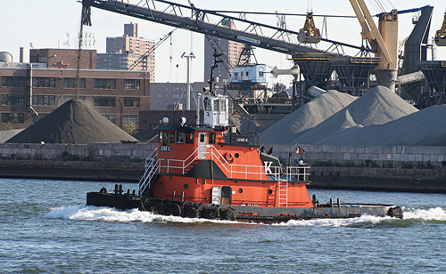A Tug Navigates The East River, Passing By A Colossal Crane