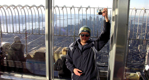 A Man Standing On The Top Of The Empire State Building
