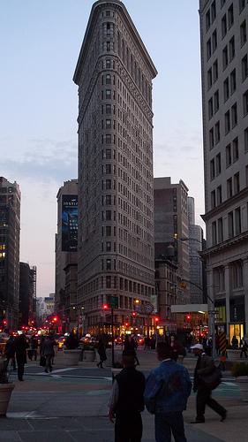 Pedestrians Pass By The Flatiron Building At Night.