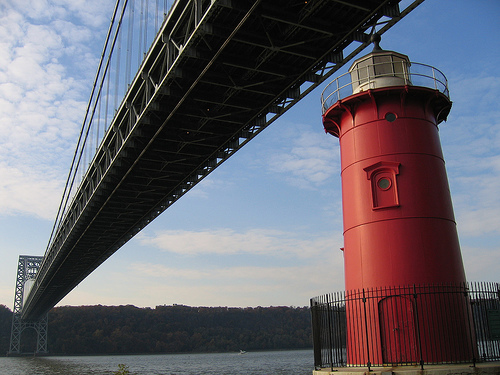 The Little Red Lighthouse Is Dwarfed By The George Washington Bridge In New York.