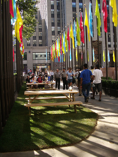 A Sunny Day At The Rockefeller Center With Many People Coming And Going