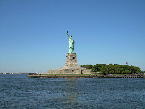 The Statue Of Liberty Standing Tall And Proud Surrounded By Both The Blue Water And Blue Sky.