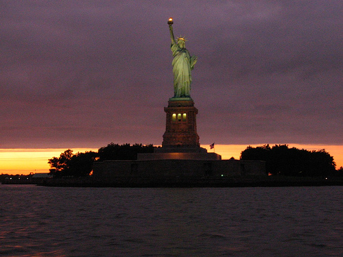 The Statue Of Liberty's Torch Greets The Night As Her Torch Glows Brightly Against The Darkened Sky