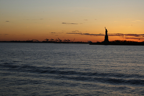 The Statue Of Liberty At Sunset, Seen From Across The Water