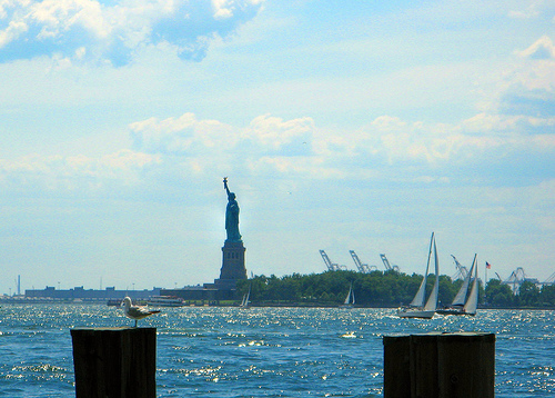 The Statue Of Liberty Welcomes Travelers As She Stands Majestically In New York Harbor.