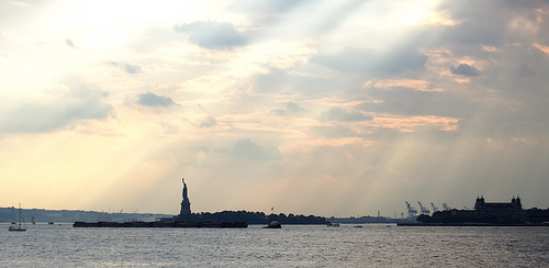 Picture Of The Statue Of Liberty, With The Sun Shining Through The Clouds.