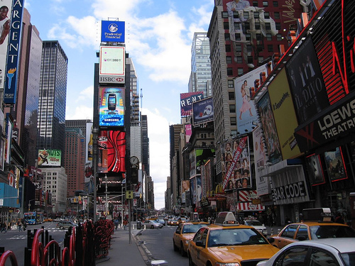 The Many Neon Signs And Traffic In Times Square, Against A Slightly Cloudy Blue Sky.