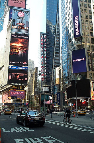 Cars, Taxis, Bicyclists, And Pedestrians Line The Streets Of Time Square