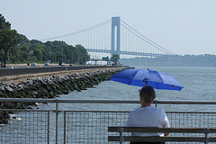 A Single Woman Sits With An Umbrella Watching The Waves In Bay Ridge, Brooklyn