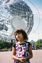 A Little Girl Poses For A Picture In Front Of The Unisphere Sculpture