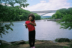 A Girl Giving Pose At The Flowing River Which Has The Arch Shaped Henry Hudson Bridge