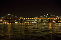 A Night Glance At The Manhattan Bridge, Reflecting A Golden Glow On East River