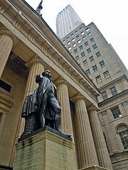 A Statue Stands Tall In Front Of The New York Stock Exchange
