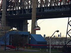 The Tram Passes In Front Of The Queensboro Bridge Between Manhattan And Roosevelt Island.