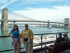 Two People Pose For A Photograph In Front Of The Brooklyn Bridge