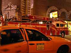 Two Staples Outside Booth Theatre, A Red Fire Truck And A Yellow Taxi