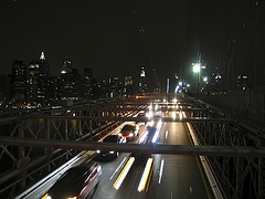 Nighttime Traffic Crossing The Brooklyn Bridge Connecting Manhattan And Brooklyn.