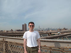 Man Posing For Picture On Brooklyn Bridge Over The East River In New York City.
