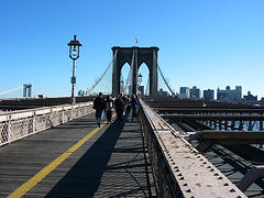 Pedestrians Walk On The Brooklyn Bridge.
