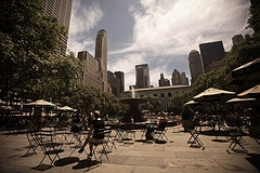 Snacking, People-watching, And Reading Library Books At The Cafe Tables Of Bryant Park