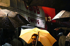 Woman With Yellow Umbrella In Front Of Now CBGB Music Club During Bad Brains Show In New York City.