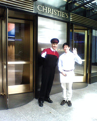 Tourist Stands With Doorman At Entrance to Christie's