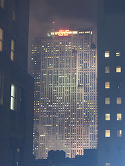 The Gem Building In The Foggy Distance Is Lit Up At Night.