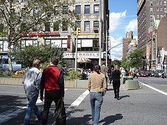People Walking In The Street Near Shih Bagels Founded By Helmer Toro In 1972.