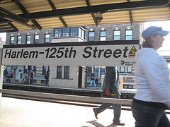 People Pass On The Street In Front Of The Harlem 125th Street Station.