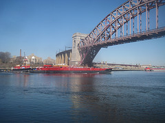 A Bright Red Boat Floats Underneath Hell Gate Bridge
