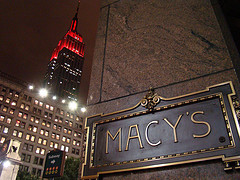A Great Upward Angle Shot Of The Macy's Plaque With The Red Lights Of The Empire State Building To The Left
