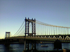 Manhattan Bridge Stretching Over The Water On A Clear Day