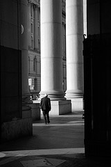 A Man Stands Among The Pillars Of Manhattan's Municipal Building