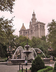 The Fountain In New York's City Hall Park, With The Municipal Building In The Background