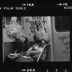 Two People Sitting On A Cool, Graffiti Tagged New York City Subway 