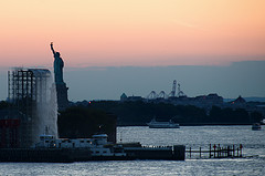 The New York Harbor In The Early Morning With The Statue Of Liberty Watching Over
