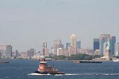 A Ferry Scoots Across The New York Harbor As The Status Of Liberty Provides A Backdrop