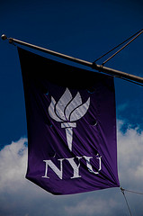 A Purple And White Flag Waves At The New York University Campus