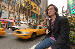 Man Sitting On The Median Outside One Times Square In View Of Mtv Studios