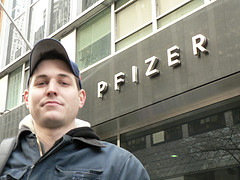 Young Man Wearing Baseball Cap In Front Of Pfizer Building.
