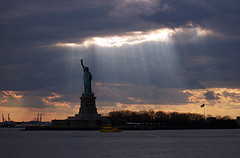 What Looks As If The Statue Of Liberty Has Pierced The Sky And Let In Some Sunshine Rays.