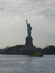 Tourist Bout In Front Of Statue Of Liberty On Cloudy Day.