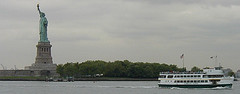 A Nice Shot Of The Statue Of Liberty On A Gloomy Day With A Ferry Going By